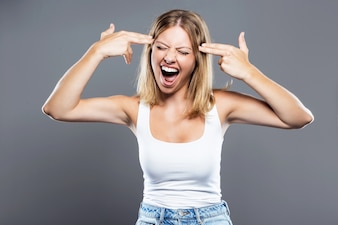 Beautiful young woman making a shooting gesture at her head over gray background.