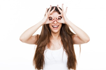 Beautiful young woman making finger glasses and smiling over white background.