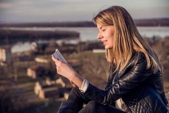 美しい若い女性は自然の本を読んで、背景には風景。リラックスした金髪の女性。ブック概念。女性が電子ブックで小説を読んで楽しむ
