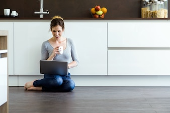 Beautiful young woman using her digital tablet in the kitchen at home.