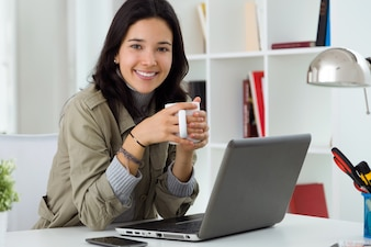 Beautiful young woman using her laptop at home.