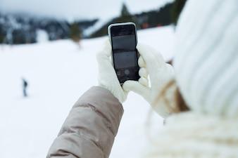 美しい若い女性は冬の背景に彼女の携帯電話を使用しています。