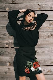 美しい若い女性は、木製の小屋で全国ウクライナの服を身に着けている