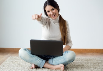 Beautiful young woman working on her laptop at home.