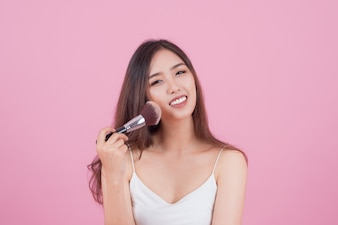 Beauty Asian Girl tan skin  with Makeup Brushes. She smiling and looking to powder brush, Natural makeup with beautiful v-shape face and long hair style.