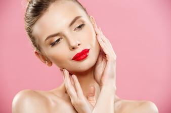 Концепция красоты - закрыть Великолепный портрет молодой женщины брюнетка. Модель красоты Девушка с яркими бровями, прекрасным макияжем, красными губами, касающимися ее лица. Изолированные на розовом фоне