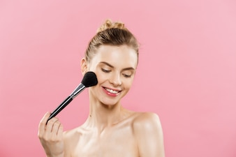 Beauty Concept - Closeup Beautiful caucasian woman applying makeup with Cosmetic Powder Brush. Perfect Skin. Isolated on pink background and copy space.