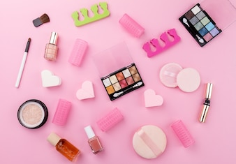Beauty Spa Feminine Concept. Different Make Up Beauty Care Essentials Cosmetics on Flat Lay Pink Background. Top View. Above.