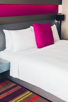 Bed with white sheets and pink cushion