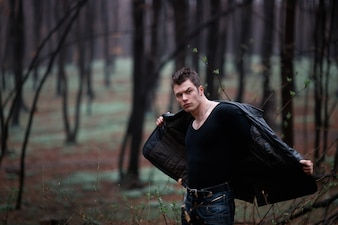 Beefy man taking off jacket in woods