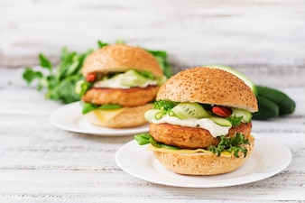 Big sandwich - hamburger with juicy chicken burger, cheese, cucumber, chili and tartar sauce on a light wooden background