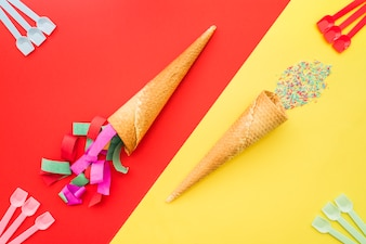 Birthday composition with decorative ice cream cones and plastic spoons