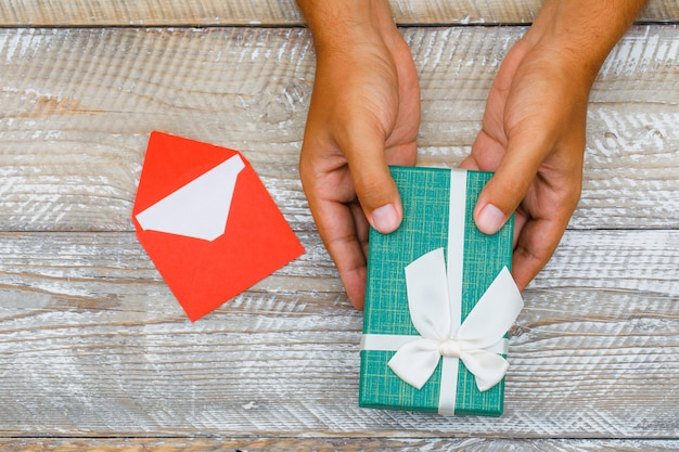 Birthday concept with card in envelope on wooden background flat lay. man passing gift box.