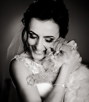 Black and white picture of happy bride holding fluffy cat behind her face