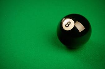 Black billiard ball on green background