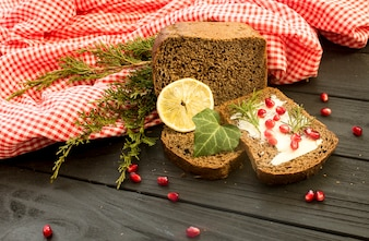 Black bread with grenades berries on a black wooden background. Christmas food, Christmas decorations with lemon, juniper, branch, red berries