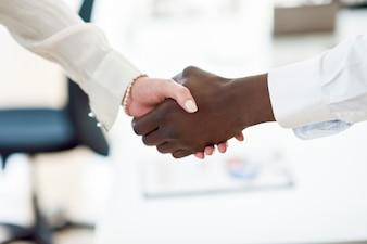 Black businessman shaking hands with a caucasian businesswoman