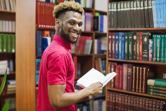 Black cheerful man in library with book