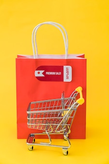 Black friday composition with cart in front of red bag