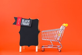 Black friday decoration with small cart next to board