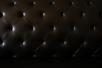 Черный кожаный диван текстуры фона.