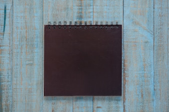 Black notebook on blue wood table