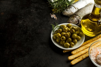 Black surface with tasty olives and other ingredients
