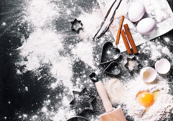 Black table full of flour and eggs with christmas decorations
