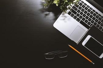 ノートパソコン、スマートフォン、メガネのある黒い作業台