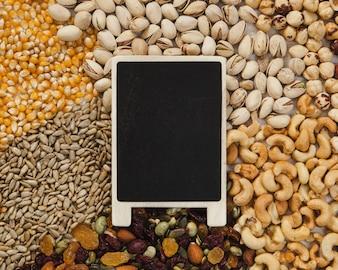 Blackboard lying on nuts and seeds