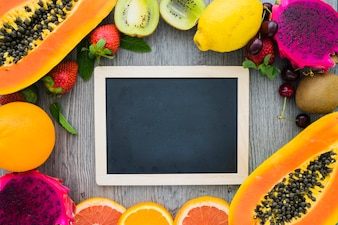 Blank blackboard surrounded by summer fruits
