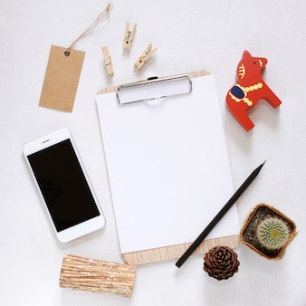 Blank clipboard and smartphone with cute decorated on workspace desk