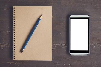 スペースと木製のテーブルの背景に広告のための空白のノートブックと電話の空白の画面。