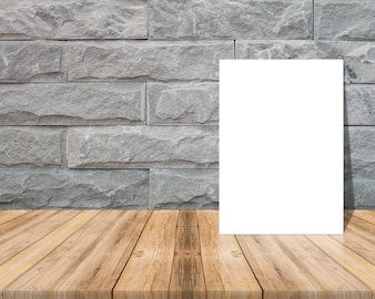 Blank paper on a wooden surface and a brick wall