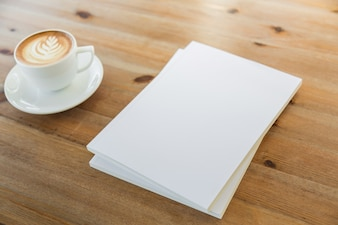 Blank pieces of paper next to a coffee