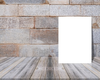 Blank sheet on a wooden table and leaning against a wall