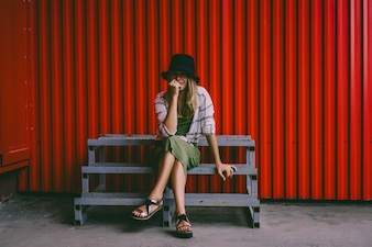 Blond girl in a hat. Street photo. A beautiful girl wearing casual clothes is smiling mysteriously. Vintage style