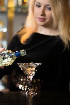 Blond girl serving alcohol drink