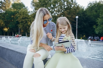 Blond mother teaching her daughter a tablet