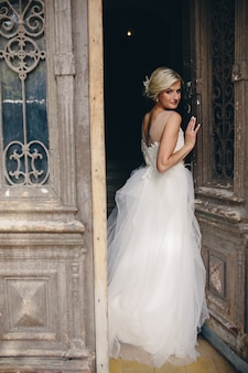 Blond woman dressed as a bride leaning on a door