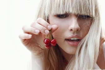 Blond woman holding cherries