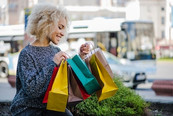 Blonde curly haired girl carrying shopping bags
