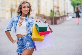 Blonde girl holding shopping bags posing outside