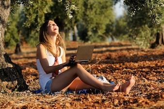 Блондинка девочка смеется с ее ноутбуком