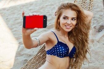 Blonde girl taking selfie on the beach