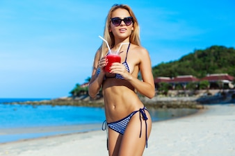 Blonde girl wearing sunglasses and holding her refreshing drink