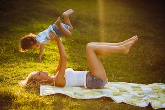 Blonde mother raises up in the sky her little son lying on grass