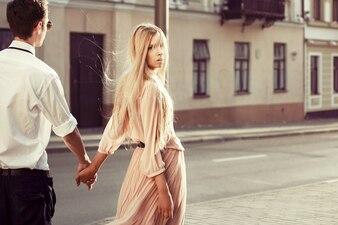 Blonde woman holding her boyfriend's hand