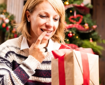 Blonde woman opening christmas gifts