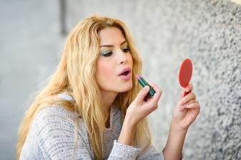 ブロンドの女性は彼女の唇を塗ると小さな鏡を保持します